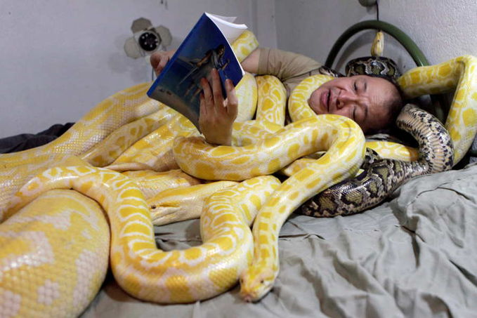 A Filipino zoo owner reads a bedtime story to his pet snakes in Manila.